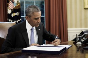 U.S. President Barack Obama signs two bills, S. 2328: Puerto Rico Oversight, Management, and Economic Stability Act and S. 337: FOIA Improvement Act of 2016, in the Oval Office of the White House in Washington, D.C., U.S., on Thursday, June 30, 2016. Obama signed the bipartisan legislation that creates a financial control board to help restructure Puerto Ricos $70 billion in debt and oversee the islands finances, marking the largest federal intervention ever into the U.S. municipal bond market. Photographer: T.J. Kirkpatrick/Bloomberg via Getty Images